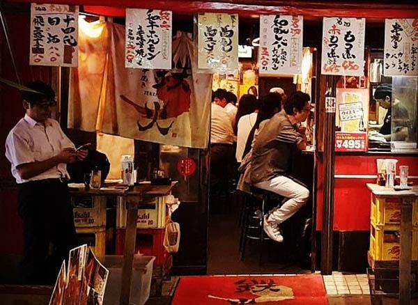 도쿄 뒷골목 술집 앞에서 한 직장인이 선 채로 맥주를 마시고 있다.