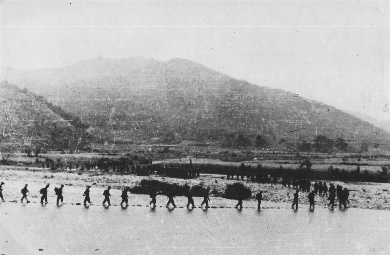 인민군들이 부교로 강을 건너고 있다.