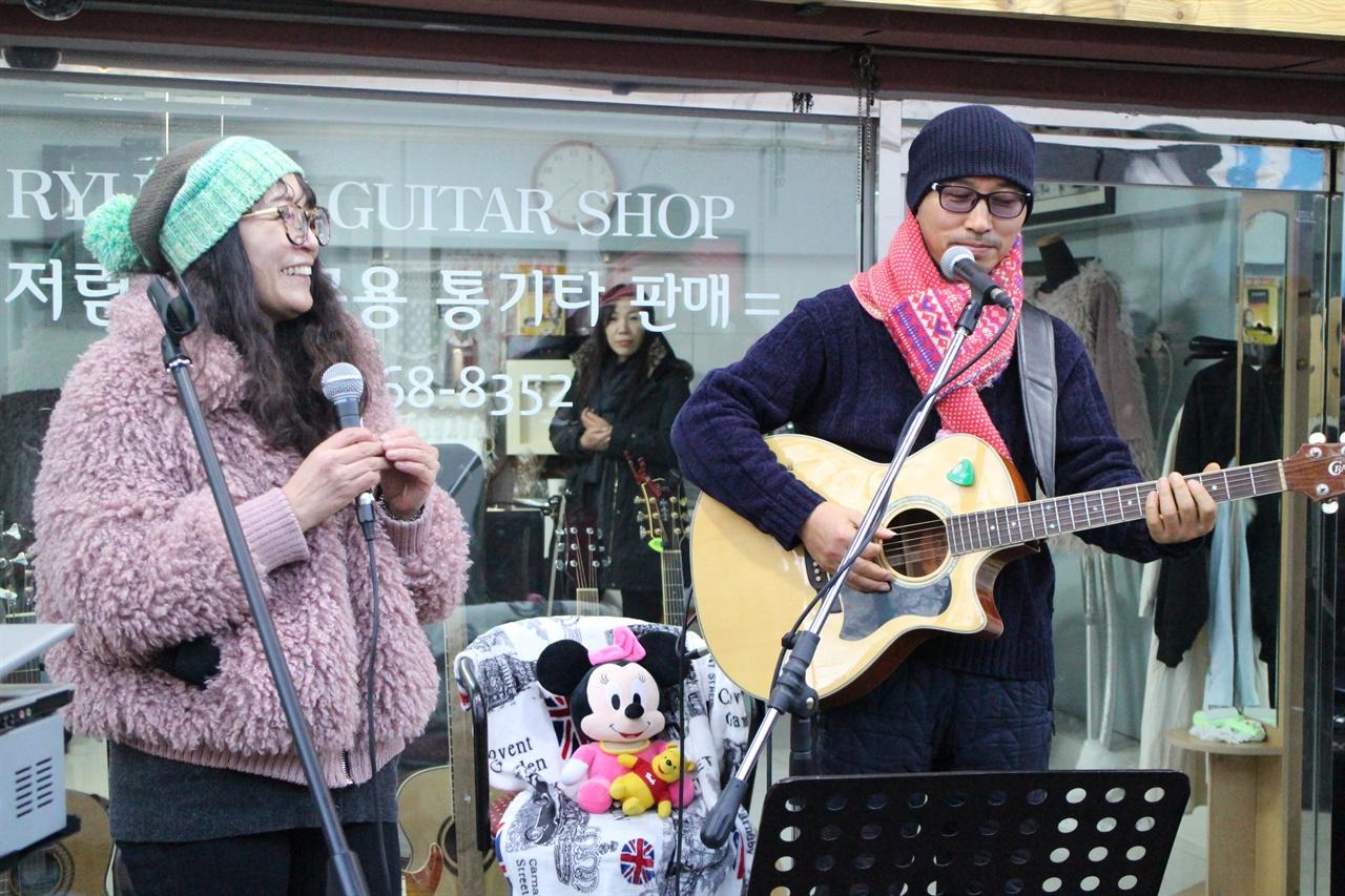 돈키호테의 멤버인 강다영, 박푸른숲씨가 노래하고 있다. 김광석을 추모하기 위해 참석한 강다영, 박푸른숲씨가 거리에서 버스킹을 하고 있는 모습이다.