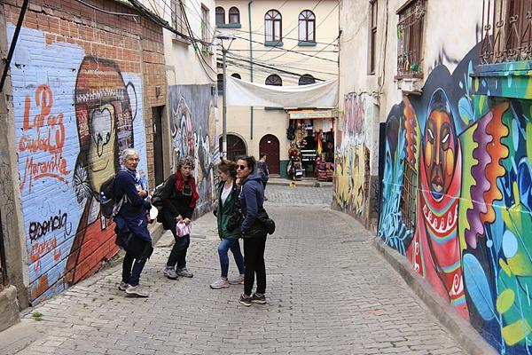 여행자들이 사가르나가 거리에서 벽화를 구경하고 있다. 오른쪽 첫번째 화려한 그림은 볼리비아를 대표하는 화가 마마니마마니의  작품이다
