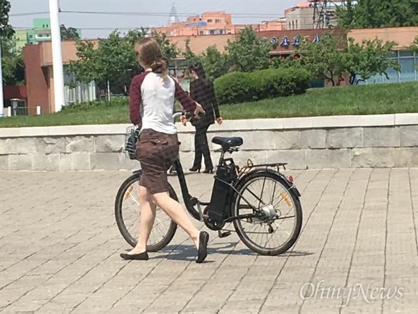 평양 길거리에서 본 외국인 거주자. 자전거를 끌고 가고 있다.