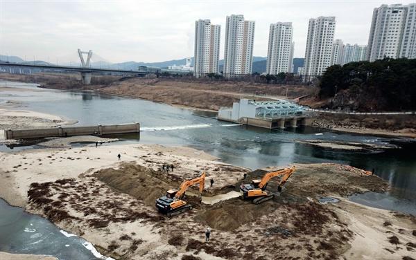 세종보 콘크리트 고정보 위쪽에서 굴착기들이 강바닥을 파헤쳐 마대자루와 천막을 수거하고 있다.
