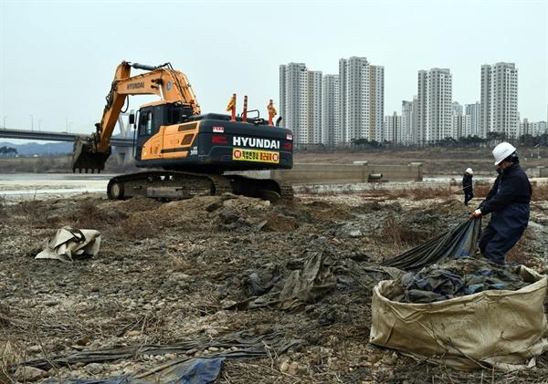 굴착기가 퍼 올린 마대와 천막은 작업자들이 수거하여 마대자루에 담고 있다.