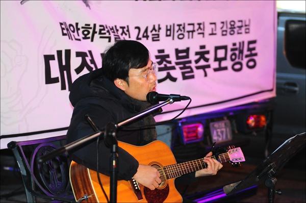 느린나무 편경열 씨가 기타를 치며 노래공연을 하고 있다.