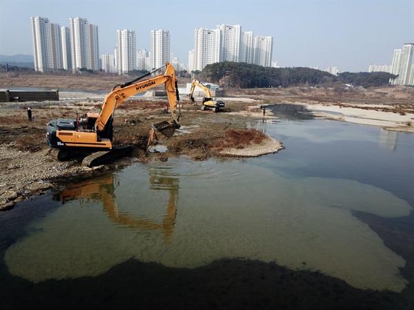 중장비가 세종보 강바닥에 묻혀있던 공사용 자재를 파헤치자 주변이 순식간에 흙탕물로 변하고 있다.