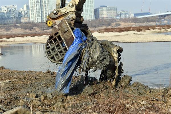 굴착기가 세종보 강바닥을 파헤치자 묻혀있던 천막과 마대자루가 줄줄이 올라왔다.