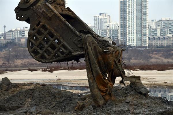 굴착기가 세종보 강바닥을 파헤치자 묻혀있던 마대자루가 줄줄이 올라왔다.