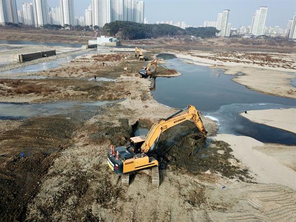3대의 중장비가 세종보 상류에 묻혀있던 4대강 사업 당시 임시물막이 마대자루와 천막을 수거하는 작업을 하고 있다.