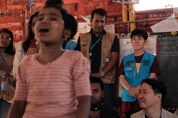 로힝야족 난민촌에 간 노희경 작가 노희경 작가가 로힝야족 난민촌에 살고 있는 아이가 러닝 스쿨에서 노래 부르고 있는 모습을 지켜보고 있다.