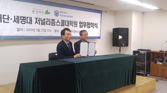 이봉수 세명대 저널리즘스쿨대학원장과 최열 환경재단이사장(왼쪽부터)이 업무협약서에 서명한 후 카메라를 향해 문서를 들어 보이고 있다.
