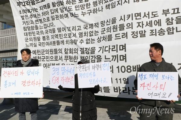 예천군민들이 1일 오전 예천군의회가 열리기 전 의회 앞에서 물의를 빚은 군의원 전원 사퇴를 촉구하는 피켓을 들고 서 있다.