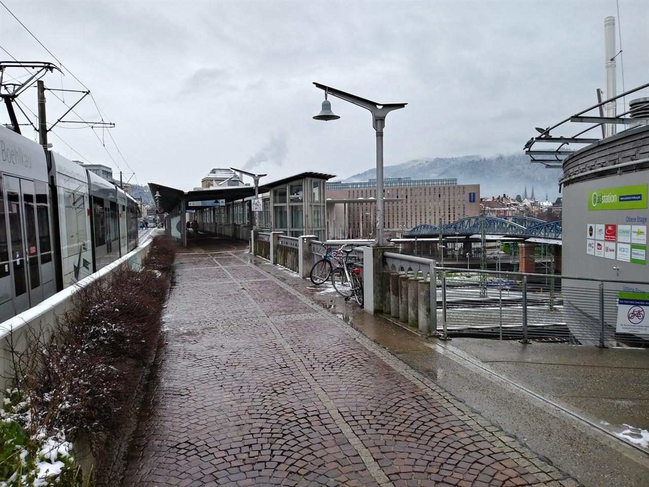 프라이부르가 '환경수도'롤 불리는 이유 기차역과 트램 정류장, 자전거 전용주차장이 곧장 연결된 모습. 트램이 달리는 육교 아래가 기차역이고, 오른편 초록색 원형 건물이 자전거 전용주차장이다.