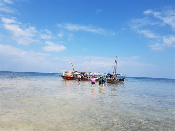 바지를 걷고 샌들을 손에 든 채로 동력 목선을 타러 가는 일행들 어촌마을에서 사파리블루까지 약 6km, 1시간 30분 정도를 배를 타고 가야 한다.