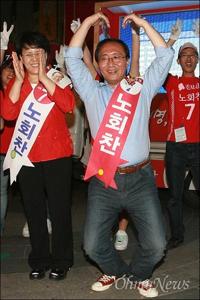 2010년 6월 1일, 노회찬 진보신당 서울시장 후보. 서울 명동입구에서 마지막 선거유세를 하며 선거운동원들과 함께 율동을 하며 하트를 만들고 있는 모습.
