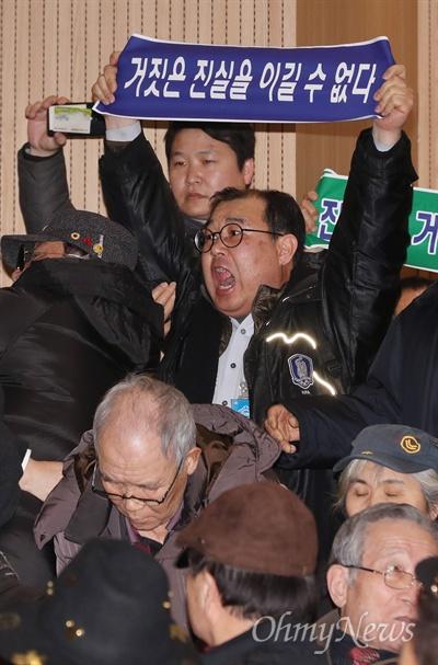 지만원에 항의하는 시민들 '5.18 북한군 개입설'을 주장하고 있는 지만원씨가 8일 오후 서울 여의도 국회 의원회관에서 자유한국당 김진태·이종명 의원 공동주최로 열린 '5·18 진상규명 대국민 공청회'에 발표자로 나서자, 이에 반대하는 시민들이 '진실은 거짓을 이길 수 없다', '광주를 모욕하지 말라'라고 적은 플래카드를 펼치며 항의하고 있다.