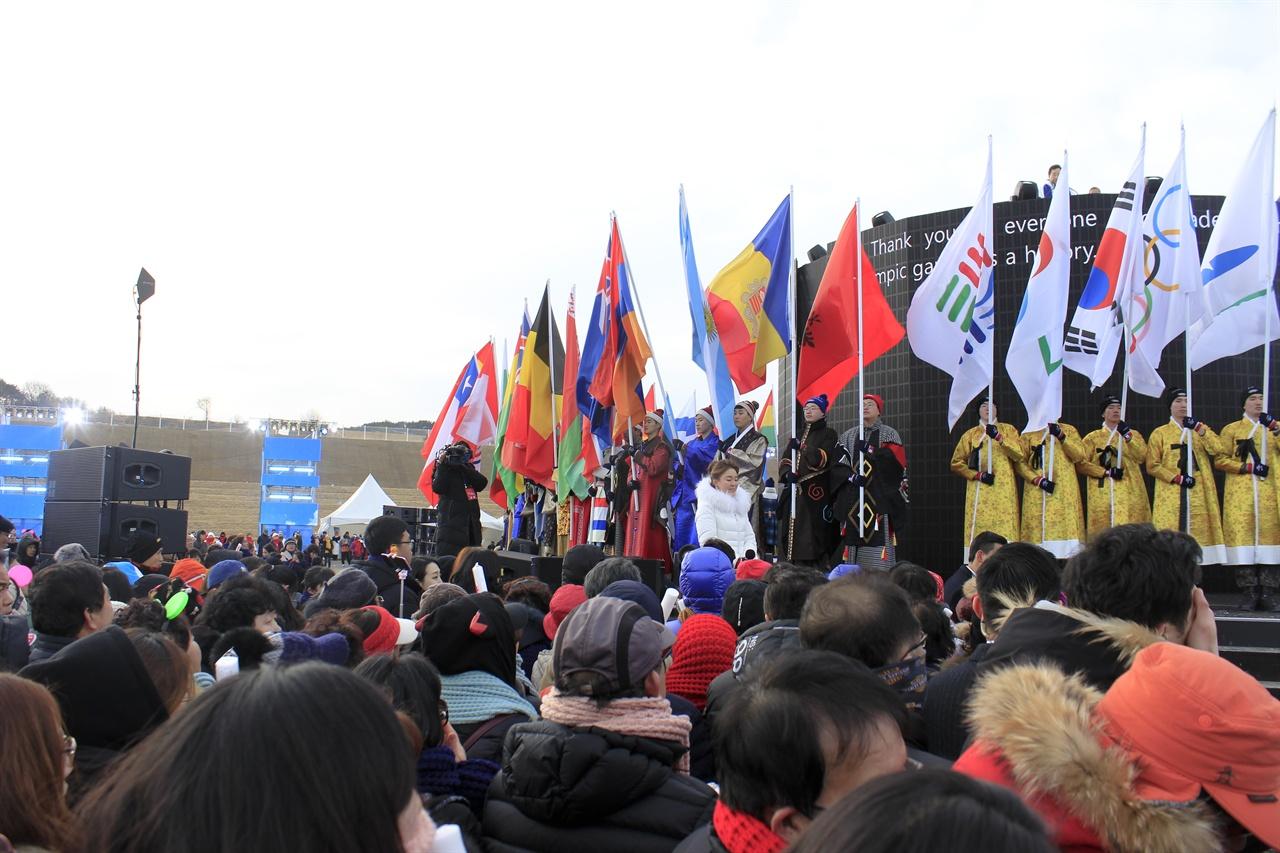 평창군기, 아지토스기, 태극기, 오륜기, 강원도기가 도열해 있다. 좌측으로는 올림픽 참가국 국기가 도열한 것이 보인다.