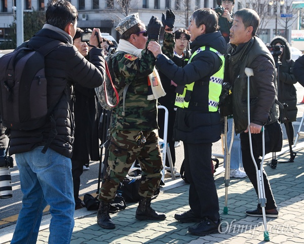 5.18 단체 기자회견장에 난입한 군복 입은 시민 13일 오후 서울 여의도 국회 앞에서 열린 5.18 망언 비호 자유한국당 해체 촉구 기자회견에 한 군복을 입은 시민이 상경한 5.18 단체 참가자와 시민들에게 다가와 욕설을 퍼붓자, 경찰이 이를 만류하고 있다.