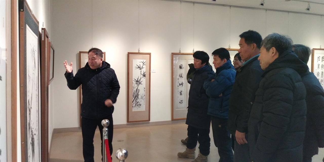 강암서예원에서   강암서예원에서 한명재 목사님의 설명을 들으며 작품을 보고 있다.