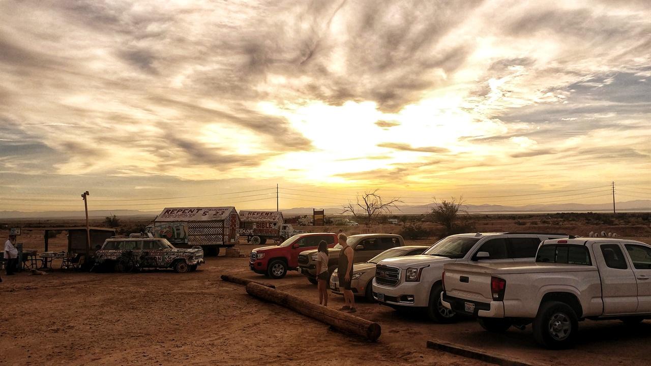 왼쪽 멀리 슬랩 시티 지역 예술가들이 판매하는 기념품 트럭이 있고 오른쪽에는 방문객들 차량이 주차돼 있다.