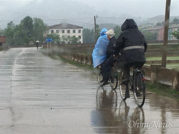 평안북도 구장군. 동포들이 우비를 쓴 채 자전거를 타고 있다.