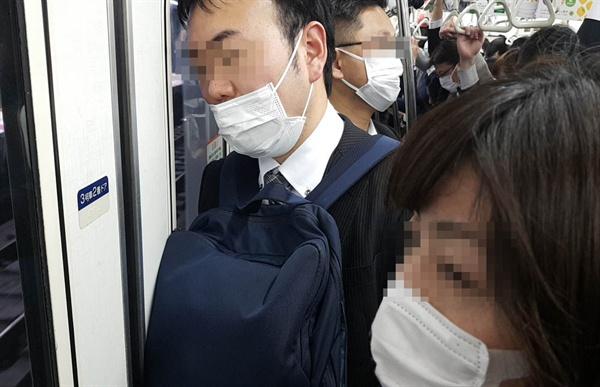 지하철 안에서 마스크를 쓰고 있는 일본 시민들. 날씨가 따뜻해지면서 점점 늘어나고 있다.