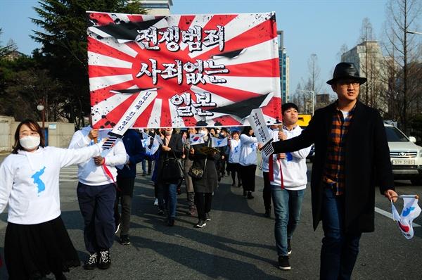 참가자들이 전쟁범죄 사죄 없는 일본을 규탄하는 내용의 퍼포먼스를 하며 행진을 하고 있다.