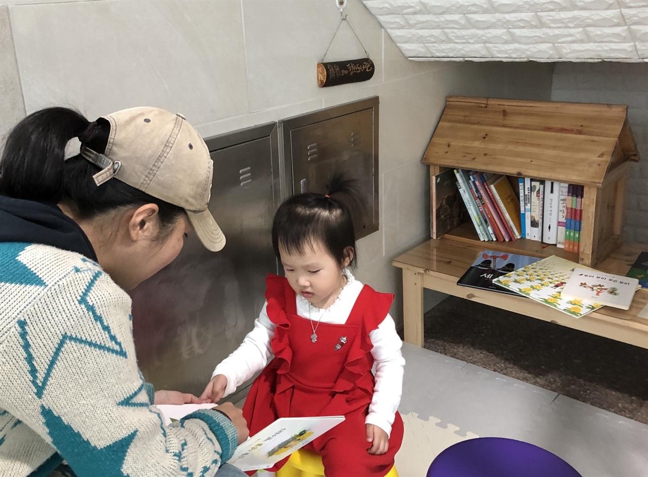모래틈같은 연립현관에 둥지 튼 꼬마평화도서관 [넝쿨넝쿨 뻗어라]를 소리내어 읽고 있는 함께 도서관장인 세 살배기 수빈이와 수빈이 엄마