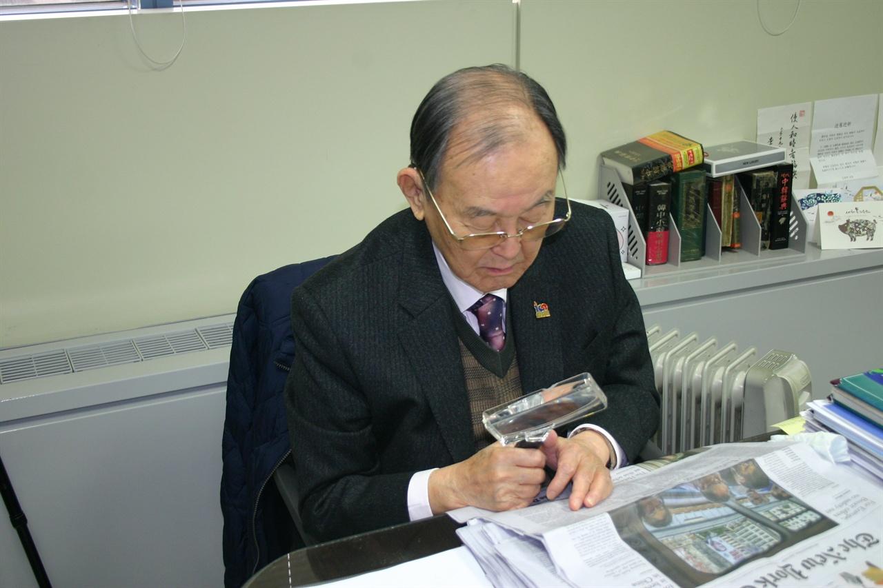 돋보기 안경에 확대경을 통해 영어신문을 보시는 김자동 회장
