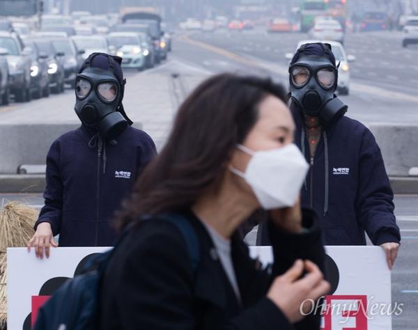 미세먼지 매우나쁨 상태가 이어지고 있는 6일 오전 서울 광화문광장에서 녹색연합이 방독면과 마스크를 쓰고 미세먼지 해결을 위해 석탄발전 중단을 촉구하고 있다.