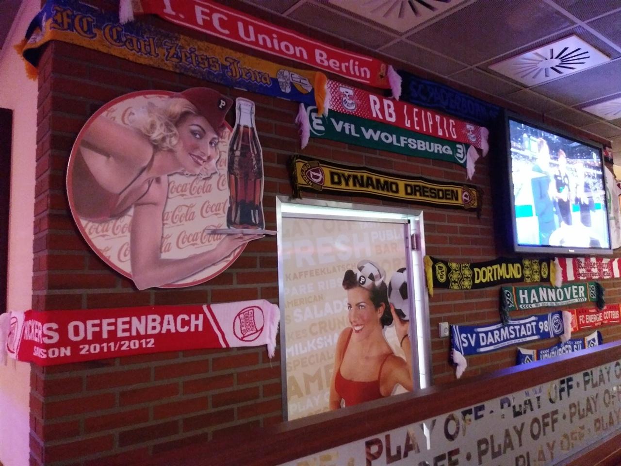 도심의 한 스포츠 바 모습 맥주를 마시면서 각종 경기를 관람할 수 있는 스포츠 바가 곳곳에 있는데, 가게 벽면에는 연고 팀의 배너(응원용 수건)가 마치 벽지처럼 붙어있다.