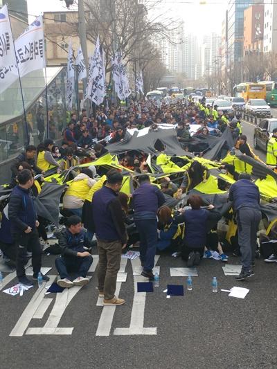 19일 오후 '재벌개혁·노동개악저지·사회대개혁 쟁취 서비스연맹 총력투쟁대회' 참석자들이 '노동개악 재벌적폐'라고 적힌 현수막을 찢고 있다.