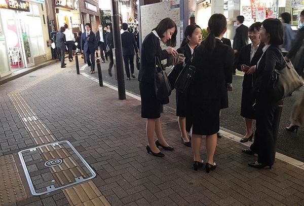 도쿄의 한 번화가에서 여자 대학생들이 이야기하고 있다.