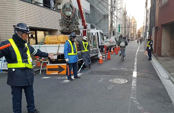 도쿄의 한 건물 공사장 앞에서 행인들을 안내하는 안전 요원들.