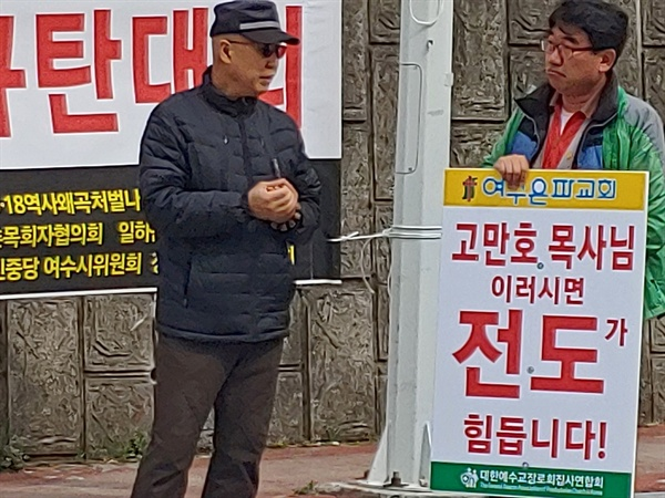 한 집회참가자가 든 '고만호 목사님 이러시면 전도가 힘듭니다'라는 피켓을 지나가는 시민이 바라보고 있다