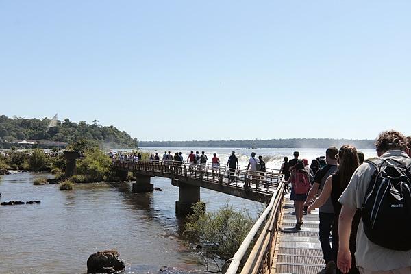 이구아수폭포로 이어지는 다리를 걸어가는 관광객들