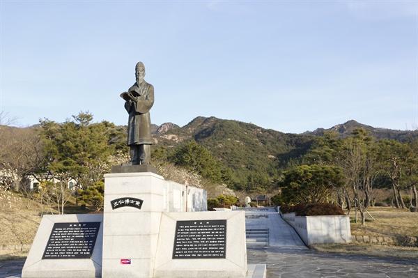 월출산을 배경으로 경서를 들고 서 있는 왕인박사의 동상. 왕인박사유적지는 그가 태어난 전남 영암에 있다.