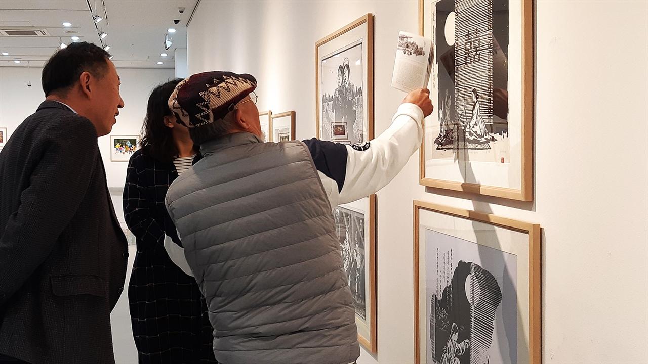 김준권 진천군립 생거판화미술관에 전시된 북한의 현대 판화 작품들을 이광균 교수와 둘러보는 김준권 작가.
