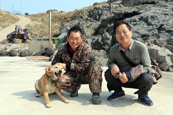 김영태 이장(왼쪽)과 목포대학교 도서문화연구원 이재언씨 모습. 이웃집 개와 혈투를 벌이고 힘들어하는 개를 주인인 김영태씨가  쓰다듬어 주고 있다