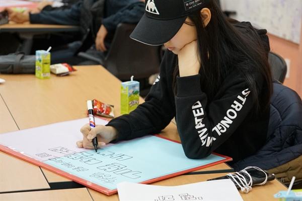 학생들이 학교와 교육당국에 바라는 내용을 스스로 손 팻말로 만들고 있다.