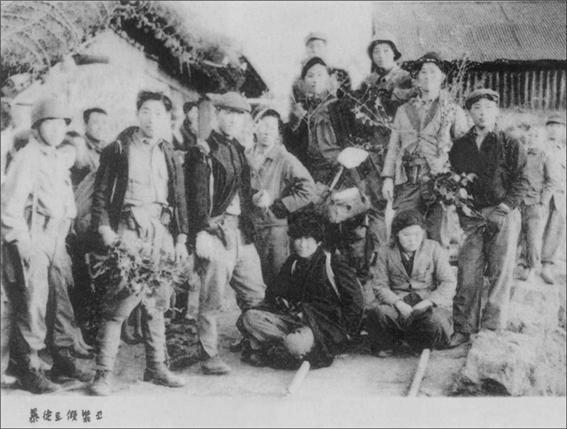 """2연대 특수부대원들의 사진 사진 왼쪽 아래에는 """"暴徒(폭도)로 假裝(가장)코'라고 씌어 있어 이들의 역할이 무엇이었는지 짐작케 한다."""