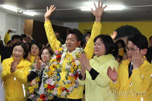 4월 3일 자정께 정의당 여영국 후보가 국회의원 보궐선거에서 당선되자 꽃다발을 걸고 손을 들어 환호하고 있다.