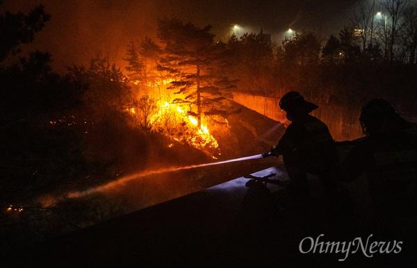 5일 오전 강원도 속초 장사동 일대 야산에 전날 강원도 고성에서 시작된 산불이 옮겨와 임야를 태우자 소방대원들이 공장으로 옮겨 붙지 않도록 물을 뿌리고 있다.