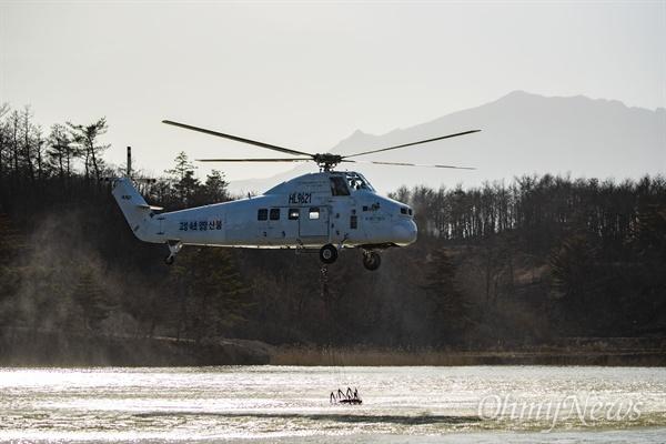 5일 오후 강원도 고성의 한 저수지에서 전날 부터 시작된 산불을 진압하기 위해 소방 헬기가 물을 보충하고 있다.
