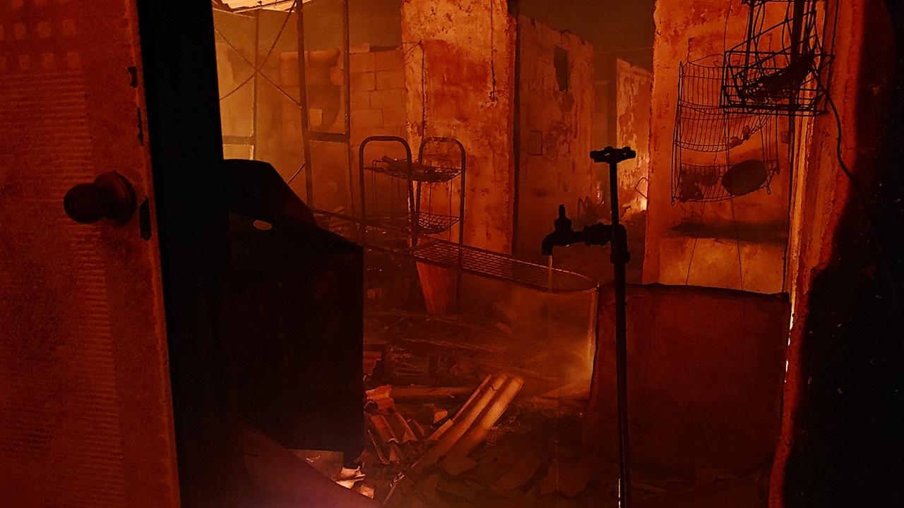 불타는 영랑호반길 민가 불은 태울 수 있으면 물이 흐르는 호스도 녹이고 결국 모두 태워버린다. 불에 탄 호스가 연결되었던 수도꼭지에서 물이 흐르고 있다.