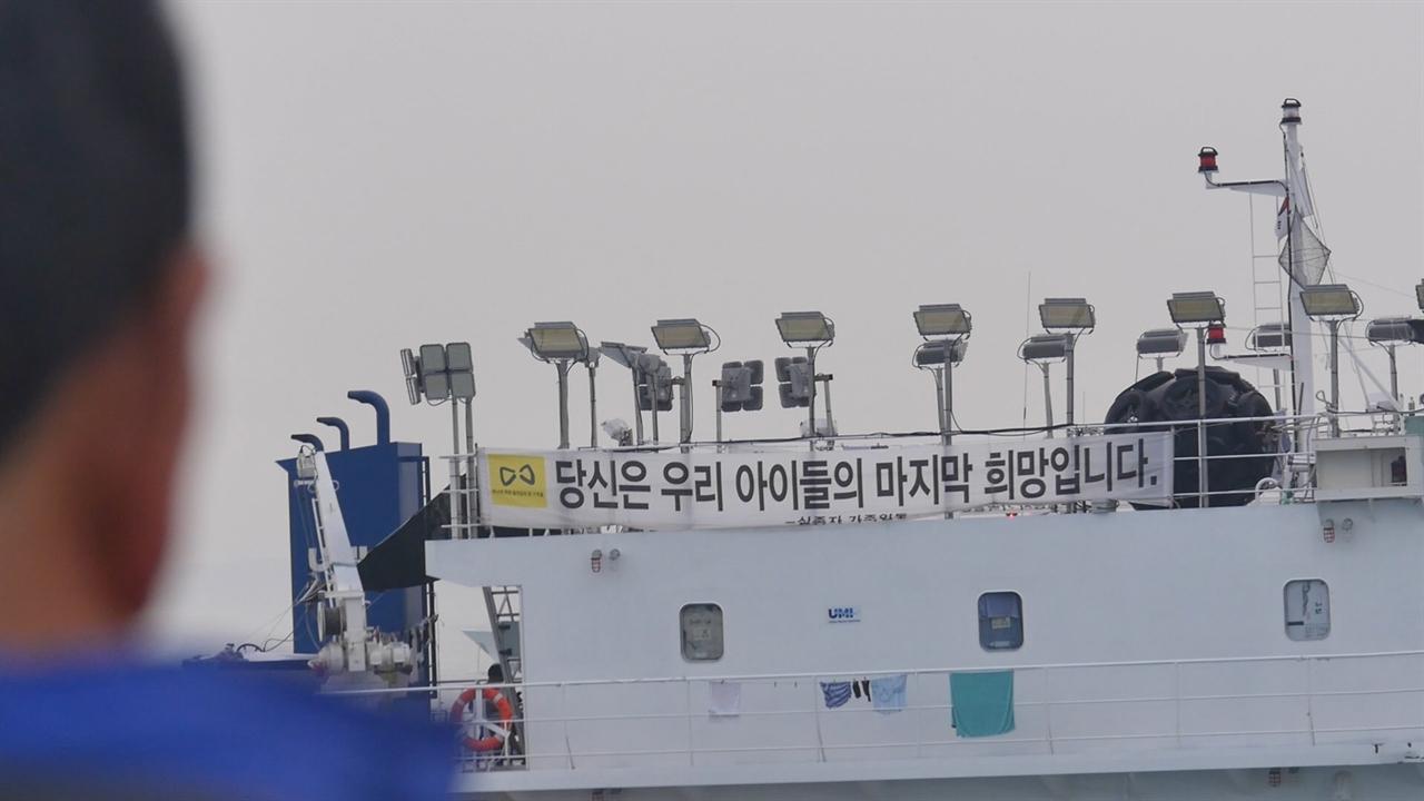 세월호 참사 당시 희생자 수습에 나서 민간 잠수사가 '당신은 우리 아이들의 마지막 희망입니다'라고 적힌 현수막을 바라보고 있다.