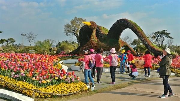 순천만국가정원을 찾은 여행자들이 비상을 꿈꾸는 흑두루미와 튤립을 배경으로 사진을 담기에 여념이 없다.