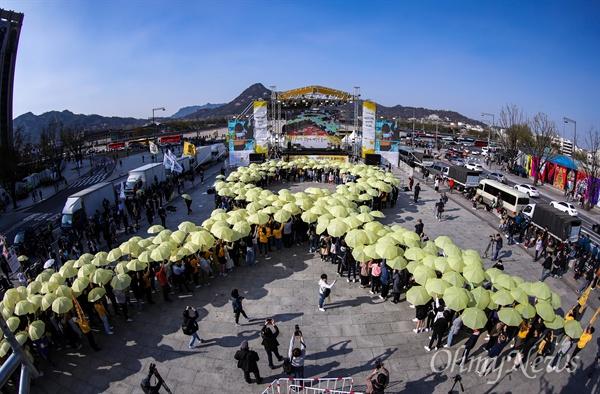 세월호참사 5주기 플래시몹 세월호참사 5주기를 앞 둔 13일 오후 서울 광화문광장에서 대학생들과 시민들이 우산을 펼쳐 세월호 기억 리본을 만드는 플래시몹을 하고 있다.