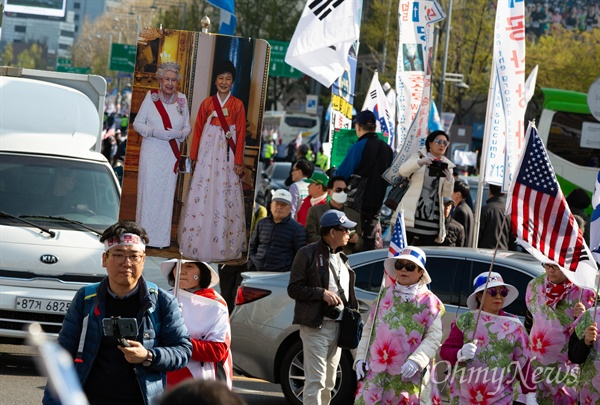 박근혜 전 대통령과 엘리자베스 영국 여왕이 함께 있는 사진을 든 대한애국당원들이 13일 오후 서울 세종로 네거리에서 '박근혜 석방'을 요구하며 행진하고 있다.