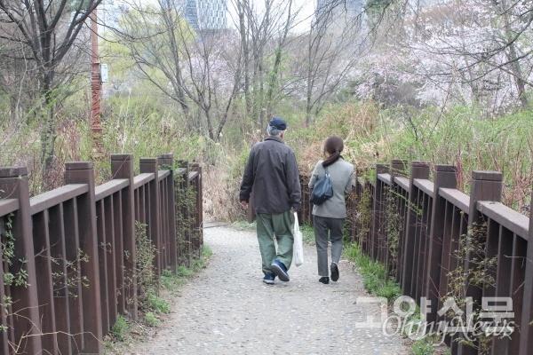 호수공원 산책로를 걸으며 대화를 나누고 있는 김훈 작가와 이영아 고양신문 대표.