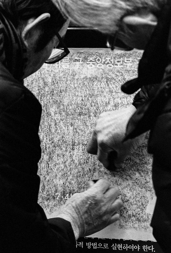 구 중앙정보부 안내판을 탁본하는 최양준, 이사영(왼쪽부터)